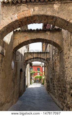 SIRMIONE ITALY - MAY 5, 2016: Picturesque narrow town street in Sirmione Lake Garda Italy.