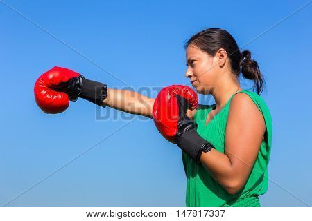 Young woman wearing red boxing gloves with blue sky