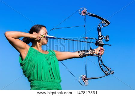 Young black haired woman aiming arrow of compound bow in blue sky