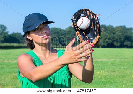 Woman with glove and cap catching baseball outdoors