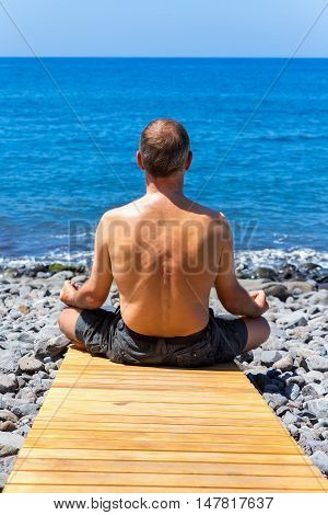 Middle aged man meditating at coast and ocean
