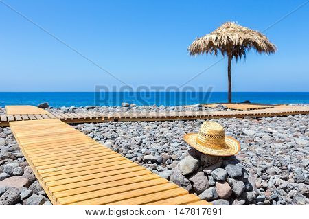 Portuguese stony coast with wooden path ocean straw hat and beach umbrella