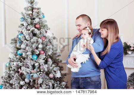 Happy father, mother and little girl smiling and looking at the Christmas tree