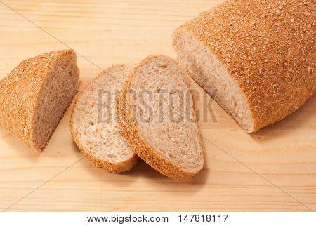 Cut bread with bran on wooden board