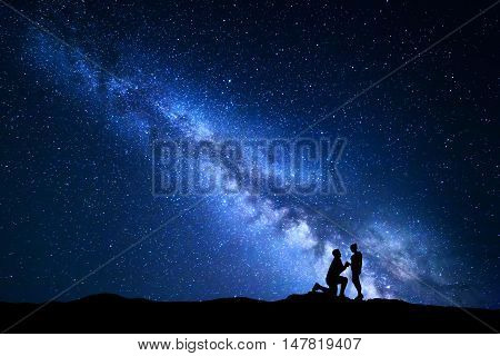 Milky Way. Night landscape with silhouettes of a man making marriage proposal to his girlfriend and starry sky. Silhouette of lovers. Couple relationship. Blue Milky way with people. Universe