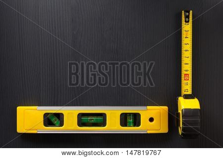 tape measure and level on wooden texture