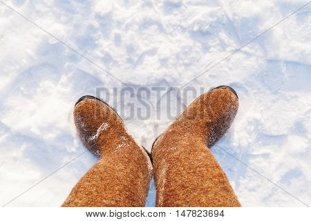 Russian traditional winter footwear - valenki. Winter sunny day top view on feet felted wool boots.