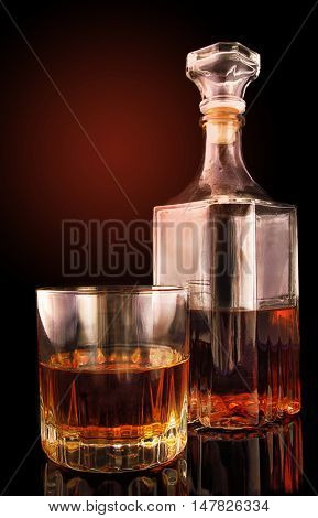 Glass with a decanter on a black surface with reflection against the background of a gradient. Vertical format. Color. Photo.