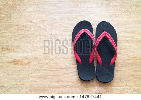 Black and red color beach slippers on wood background.