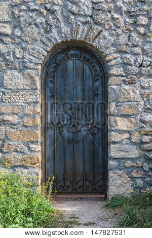 Heavy closed black metal door on a stone wall of a medieval fortress, made of riveted wood