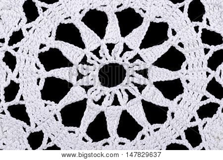 Star in a white crocheted doily. Crochet is a process of creating fabric by interlocking loops of yarn  using a crochet hook. Macro photo close up from above on black background.