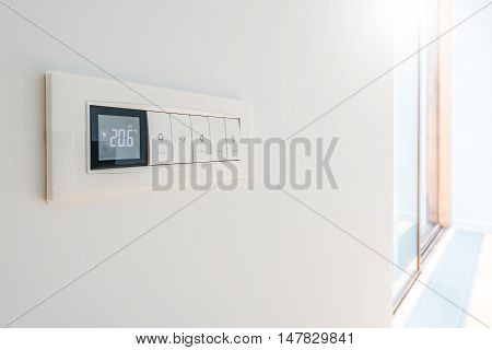 Wall display shows air temperature inside the apartment room.