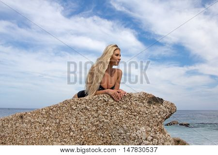 A pretty blonde in a one piece swimsuit relaxing on a boulder att he beach looking at the sea