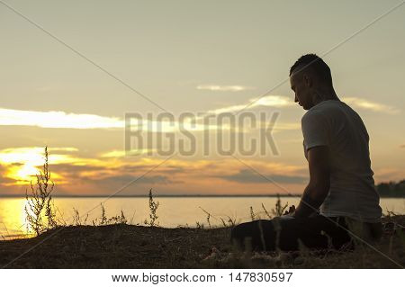 Silhouette of young man sitting on beach at sunset on yoga meditation pose