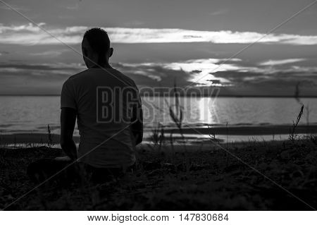 Silhouette of young man sitting on beach at sunset and practicing yoga. Meditation pose. Black and white image