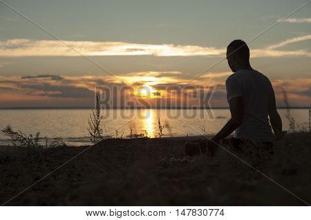 Young man sitting on the beach and doing yoga meditation pose.
