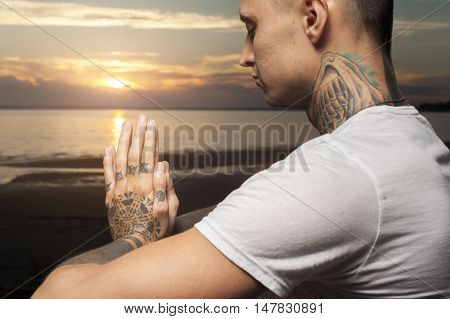 Cropped shot of young tattoo man practicing yoga on the beach at sunset. Meditation Pose.