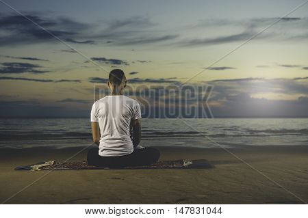 Young tattoo man sitting on the beach, meditating and doing yoga lotus posittion. Meditation Pose.