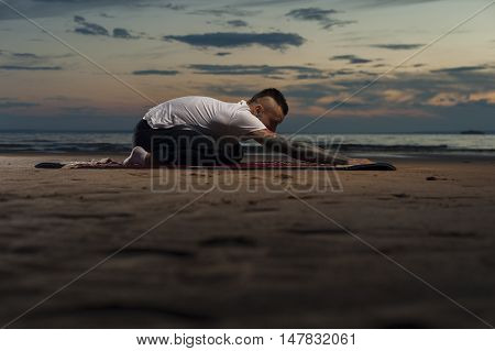 Flexible young man with tattoos doing stretching exercises on the beach. Yoga practice outdoors. Summer time, sunset