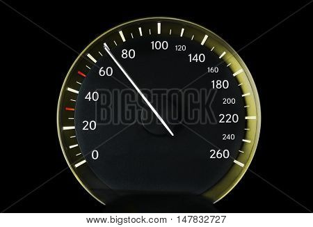 Speedometer of a car showing 70, glowing yellow