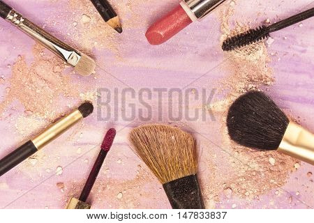 Makeup brushes, lipctick and pencil on a light purple background, with traces of powder and blush on it.