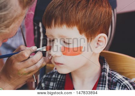 Child animator, artist's hand draws face painting to little boy. Child with funny face painting. Painter makes tiger eyes on boy's face. Children holiday, event, birthday party, entertainment.