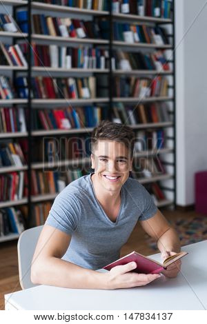 Young man with book in library
