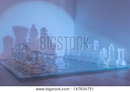 Closeup och chess board with glass pieces In light blue haze. Chess pieces in Clear and frosted glass with large shadows on the wall