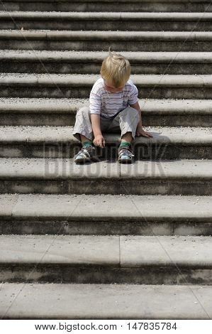 Little Boy sitting on stone steps in park. Loneliness, melancholy, stress.