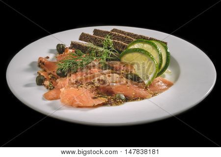 Sliced salmon salted filet with lemon black bread on white plate