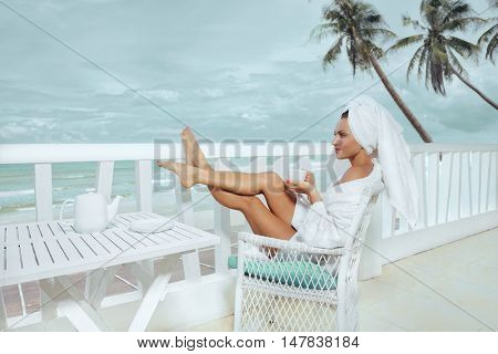 Woman drinking coffee in hotel terrace over sea view