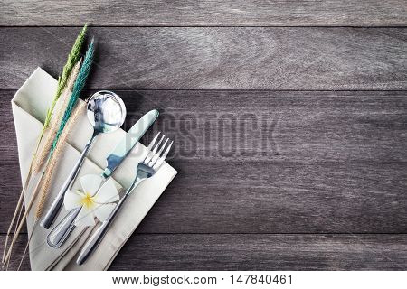 Silverware with a flower on rustic wooden background. Vintage color filtered.