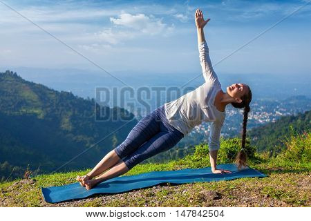 Yoga outdoors - beautiful sporty fit woman doing yoga asana Vasisthasana - side plank pose in mountains