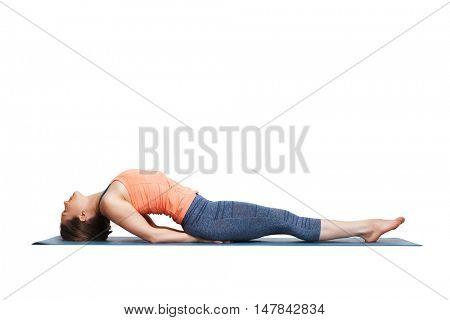 Beautiful sporty fit yogini woman practices yoga asana Matsyasana - fish pose variation in studio isolated on white