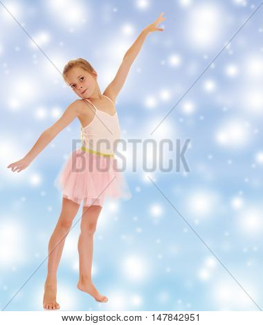 Charming little girl ballerina in a pink translucent dress.On a blue background with large, white, Christmas or new year's snowflakes.