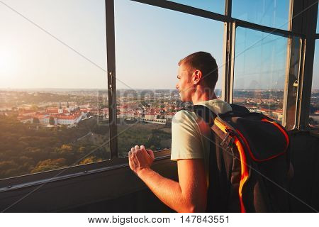 Young tourist looking on the historical part of Prague Capital. Strahov Monastery and park under Petrin hill at the amazing sunset.