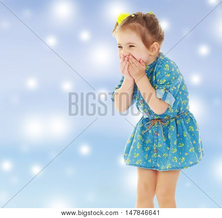Cute little girl in a short blue dress terrified has closed hands the person. Close-up.Gentle blue Christmas background with white snowflakes abstract.