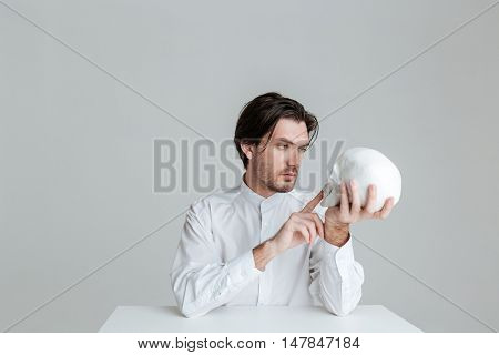 Young man sitting at the table and pointing finger at fake skull in hands isolated on the gray background