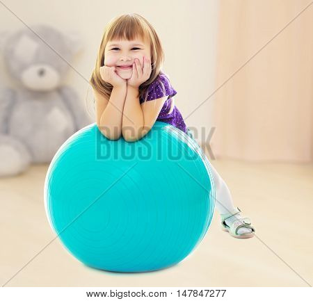 About what dreams a little girl , put his hands on big blue fitness ball.In the children's room where sits a large Teddy bear .
