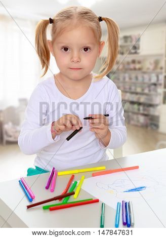 The concept of family happiness, and preschool education of the child , against a child's room with bookshelves.Pretty little blonde girl drawing with markers at the table.Girl holding in hands