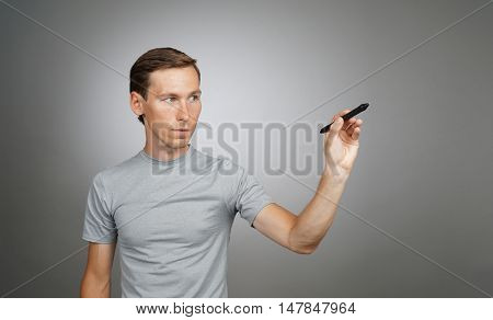 Man writing something with marker on glass board.
