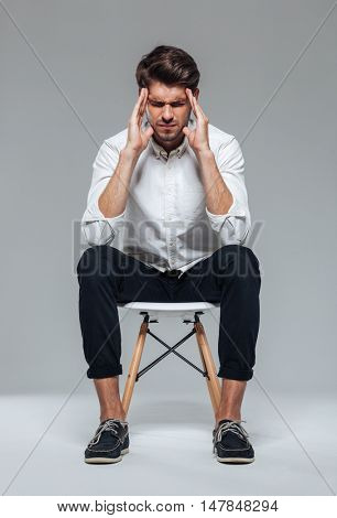 Stressful depressed man touching his temples and having headache over gray background