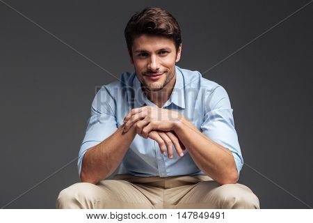 Close up portrait of a smiling happy handsome man in blue shirt sitting on the chair over grey background