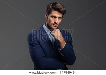 Thoughtful young brunette man in blue jacket thinking about something isolated on a gray background