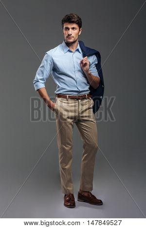Handsome businessman holding his jacket over shoulder with hand in pocket on gray background