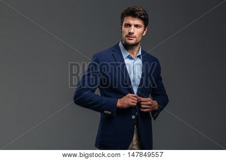 Confident businessman putting on blue jacket isolated on a gray background