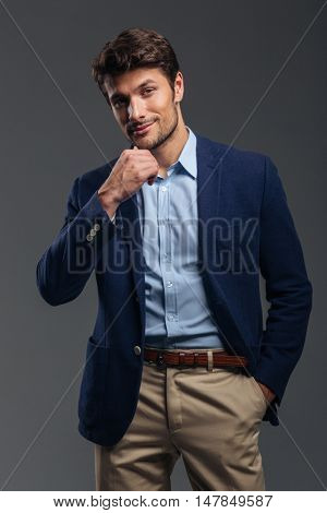 Handsome young pensive businessman thinking about something wuth hand in pocket isolated on the gray background