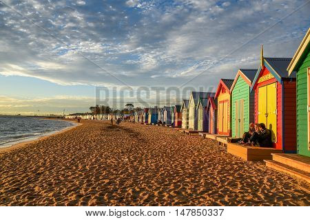 MELBOURNE AUSTRALIA - JULY 18 2016 : Tourists sit on deck of bathing boxes at Brighton Beach near Melbourne Australia.