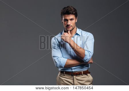 Handsome serious man looking at camera isolated on a gray background