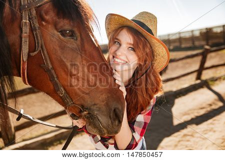 Portrait of happy beautiful young woman cowgirl in hat with her horse on ranch